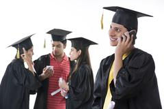 Smiling graduate student answering mobile phone with friends discussing over Stock Photos