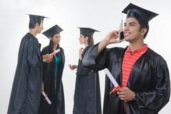 Happy graduate student answering smart phone with friends discussing against Stock Photos