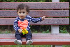 Full length of innocent girl with toy pointing sideways while sitting on park Stock Photos