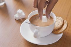 Cropped image of woman adding sugar cube to tea Stock Photos