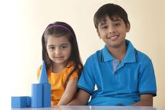 Portrait of smiling siblings with geometric shapes on table against colored Stock Photos