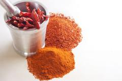Crushed red chili peppers with chilies in mortar and pestle over white Stock Photos