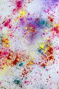 Multi-colored powder paint spread over white background Stock Photos