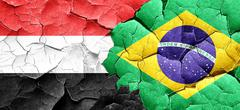 Yemen flag with Brazil flag on a grunge cracked wall Stock Illustration