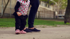 Child's legs walking near parent legs. Happy family walking together Stock Footage