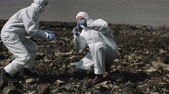 Forensic scientist examining sample at river bank Stock Footage