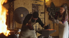 Cutting metal by hand forging with help of two people Stock Footage