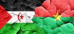 Western sahara flag with Burkina Faso flag on a grunge cracked w Stock Illustration