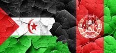 Western sahara flag with afghanistan flag on a grunge cracked wa Stock Illustration