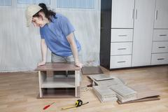 Assemble furniture, carpenter apply glue and clamp two boards together. - stock photo