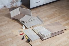 Putting Together Self Assembly Furniture chipboard parts lie on floor. - stock photo