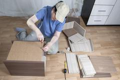 Furniture assembly, woman fastens sheet hardboard in back bedside table. - stock photo