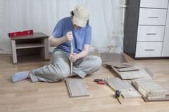 Assemble wooden furniture, a woman applies glue to chipboard edge. - stock photo
