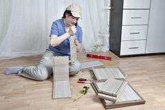Woman fasten board drawer, using glue, assembly of wooden furniture. Stock Photos