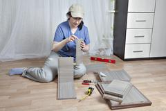 Woman nightstand assembly, bonding parts of the drawer. - stock photo