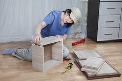 Woman putting together board drawers, furniture assembling at home. Stock Photos