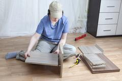 Woman putting together self assembly furniture assemble flat-pack. Stock Photos
