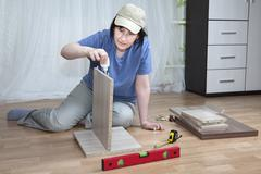 Furniture assembly, woman lubricates surface of adhesive chipboard. - stock photo