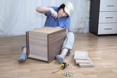 One Caucasian woman self assembly new furniture sitting on floor. Stock Photos