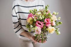 Rich bunch of pink eustoma and roses flowers, green leaf in hand Fresh spring Stock Photos