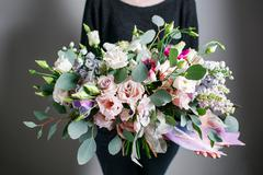 Rich bunch of flowers, green leaf in hand Fresh spring bouquet. Summer - stock photo