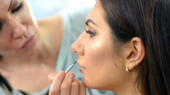 Makeup artist apply makeup to an attractive young woman - stock footage