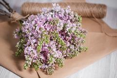 Empty postal envelope and bouquet of lilac flowers on the white wooden Stock Photos