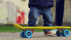 Baby on skateboard. Child legs ride on skate in outdoor Stock Footage