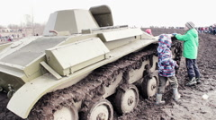 Children Playing With Standing Tank Near The Caterpillar Stock Footage