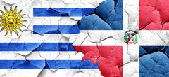 Uruguay flag with Dominican Republic flag on a grunge cracked wa - stock illustration