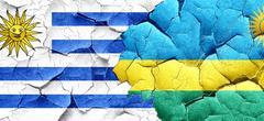 Uruguay flag with rwanda flag on a grunge cracked wall - stock illustration