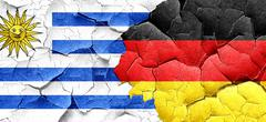Uruguay flag with Germany flag on a grunge cracked wall Stock Illustration