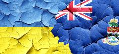 Ukraine flag with Cayman islands flag on a grunge cracked wall - stock illustration