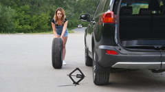 Pretty girl replacing tyres - stock footage