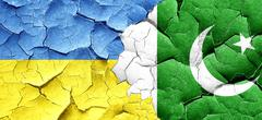 Ukraine flag with Pakistan flag on a grunge cracked wall - stock illustration