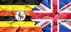 Uganda flag with Great Britain flag on a grunge cracked wall - stock illustration