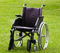 Empty wheelchair on grass field Stock Photos