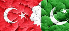Turkey flag with Pakistan flag on a grunge cracked wall - stock illustration