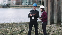 Engineers working on a Wind Turbine project at river bank Stock Footage
