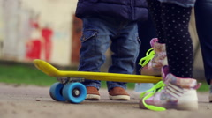 Children playing with skateboard and trying to ride. Kids having fun outdoor - stock footage