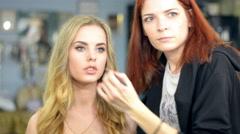 Make-up artist applying eyelash makeup to model's eye. Close up view. - stock footage