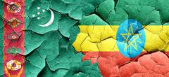 Turkmenistan flag with Ethiopia flag on a grunge cracked wall - stock illustration