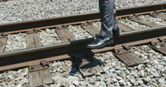 Balancing Act of Life on Train Tracks Young Business Man Close, 4K Stock Footage