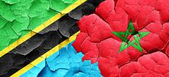 Tanzanian flag with Morocco flag on a grunge cracked wall - stock illustration
