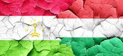 Tajikistan flag with Hungary flag on a grunge cracked wall - stock illustration