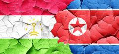 Tajikistan flag with North Korea flag on a grunge cracked wall - stock illustration