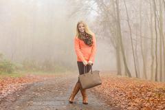 Happy fashion woman with handbag in autumn park - stock photo