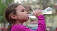 Child drinking water from bottle outdoor. Young girl with water bottle in hand Stock Footage
