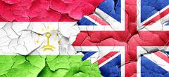 Tajikistan flag with Great Britain flag on a grunge cracked wall - stock illustration