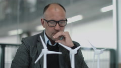 Business people examining wind turbine models in office Stock Footage